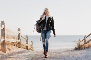 אישה בז'קט עור הולכת על חוף הים