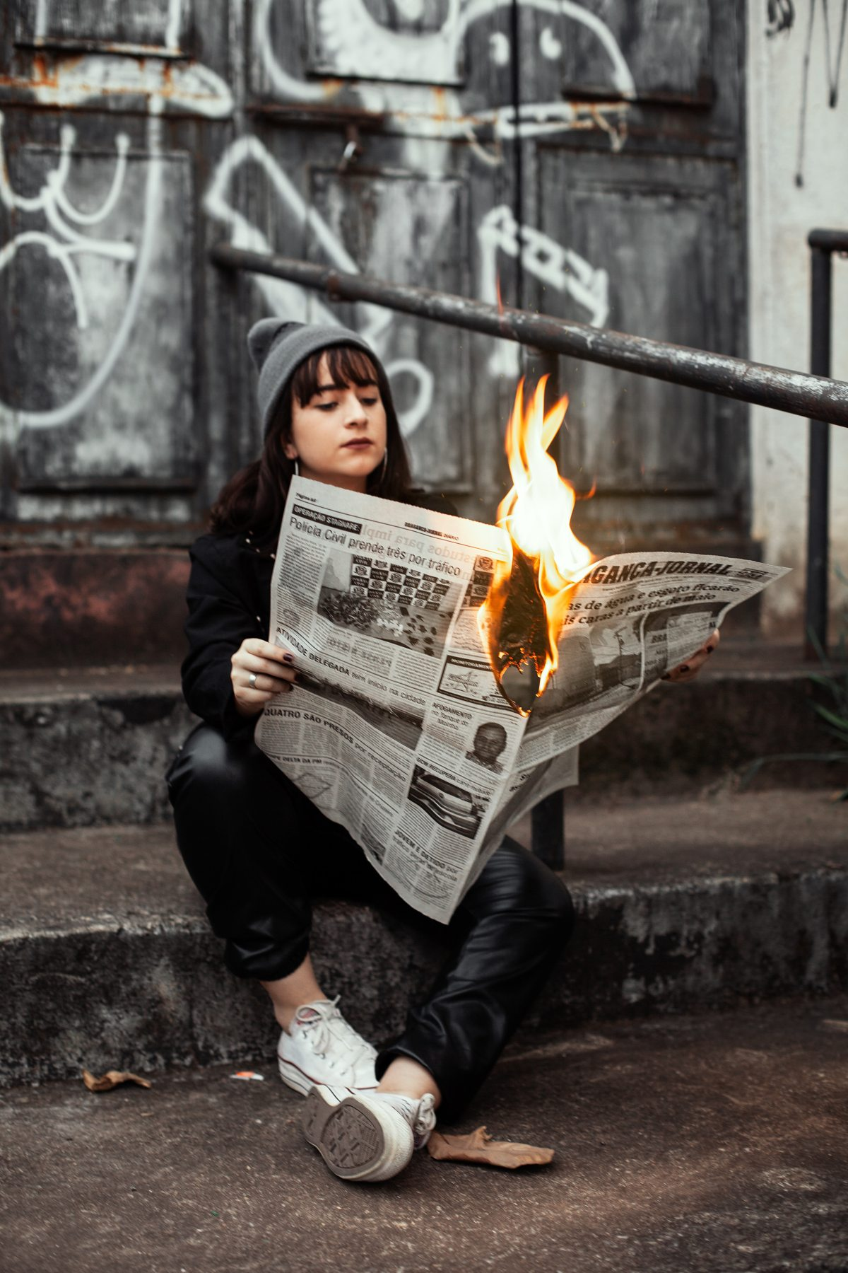woman holding a burning newspaper