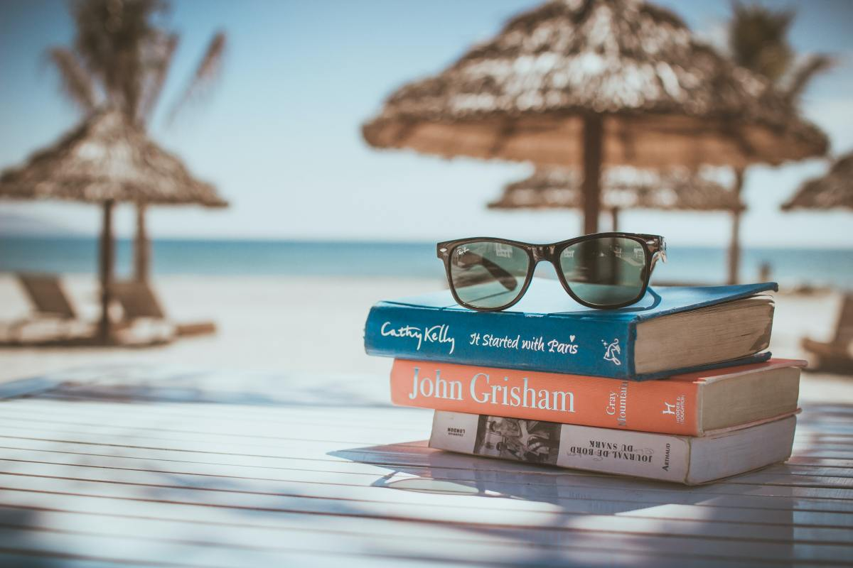glasses on top of books at the beach